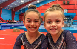 Two girls smiling at a competition in unitards.