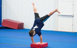 A boy doing a handstand on a mat.