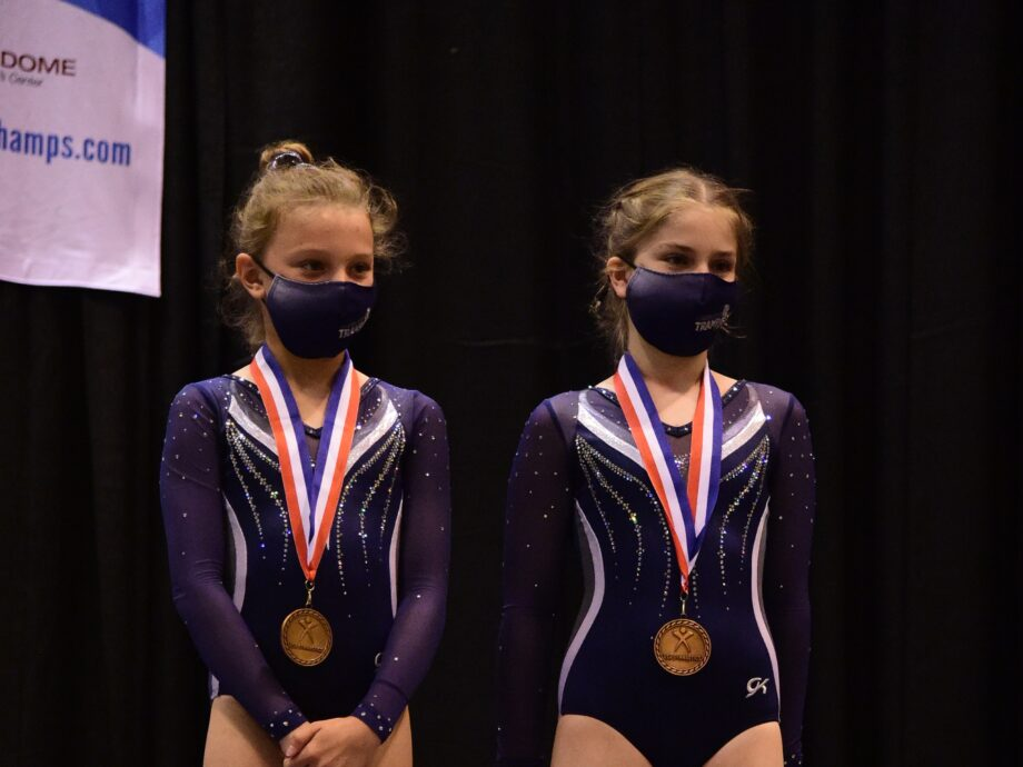 Two girls stand at a podium with medals.