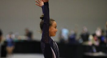 A gymnast salutes after a routine.