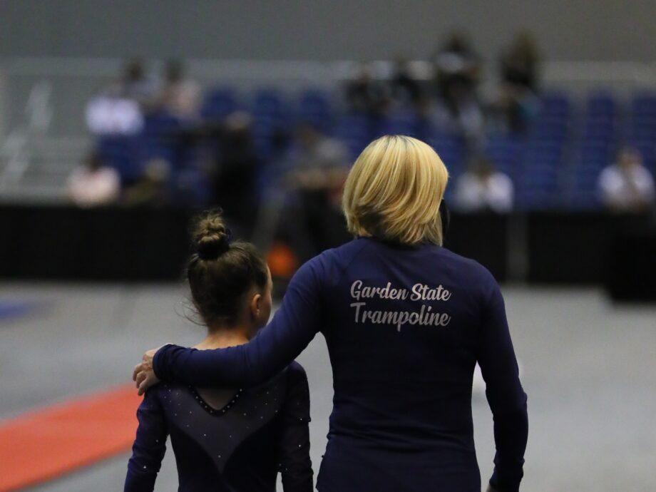 Coach Natasha walks with a gymnast.