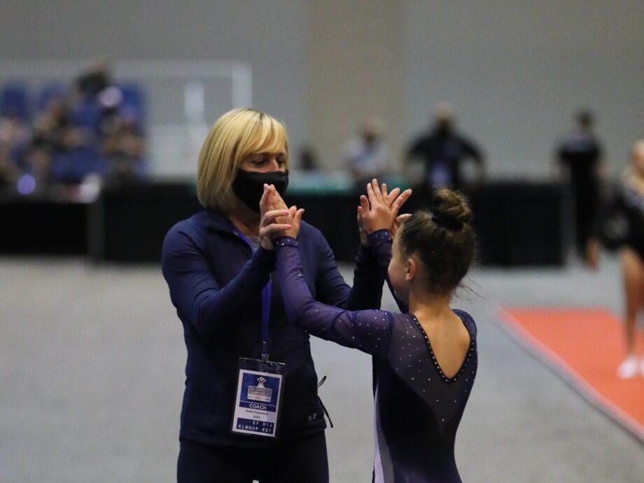 Coach Natasha congratulates a gymnast.