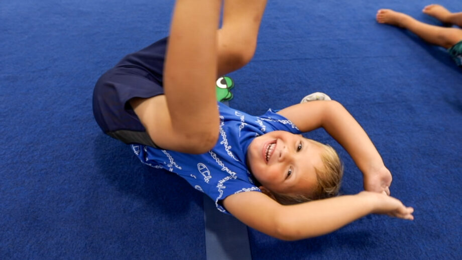 A boy on the floor smiling at the camera.