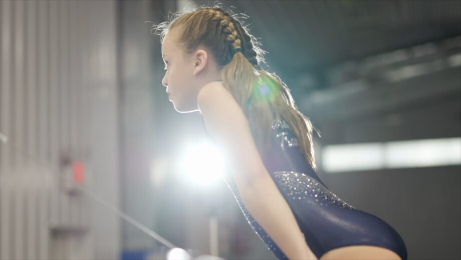 A close up of a girl on the uneven bars.