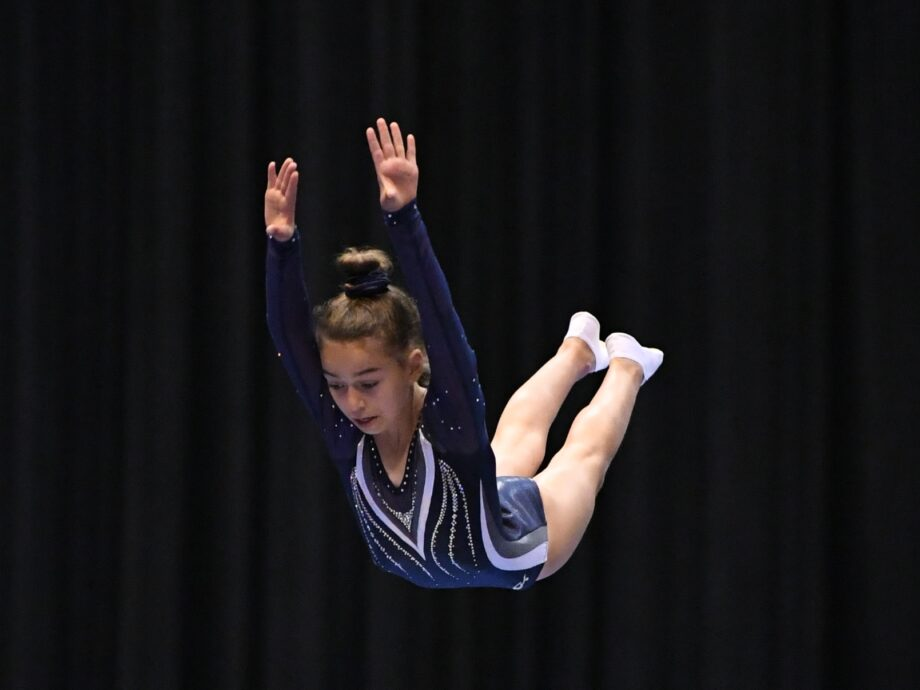 A girl keeps her posture while mid-air on trampoline.