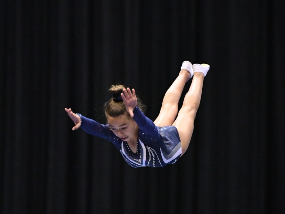 A girl in the air, landing from a flip.