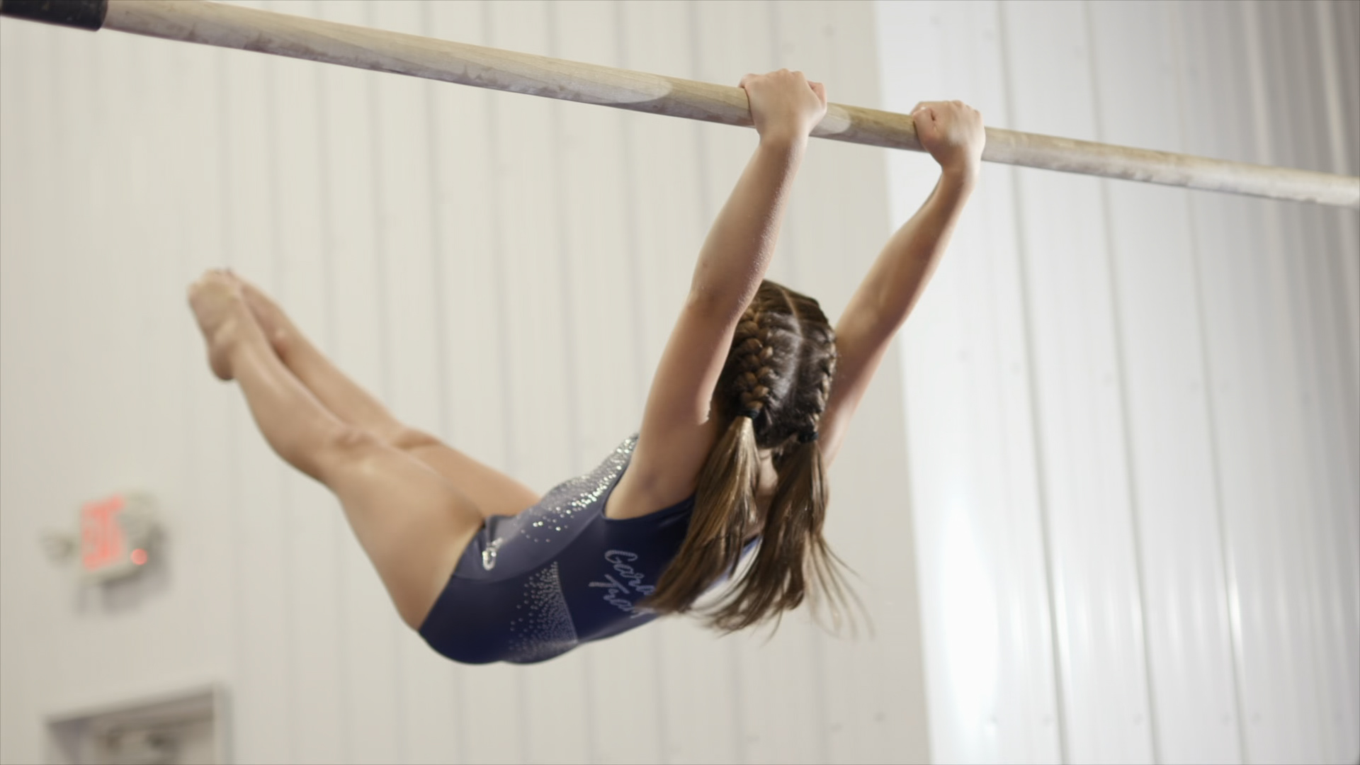 a girl swinging on the uneven bars with her feet pointed.