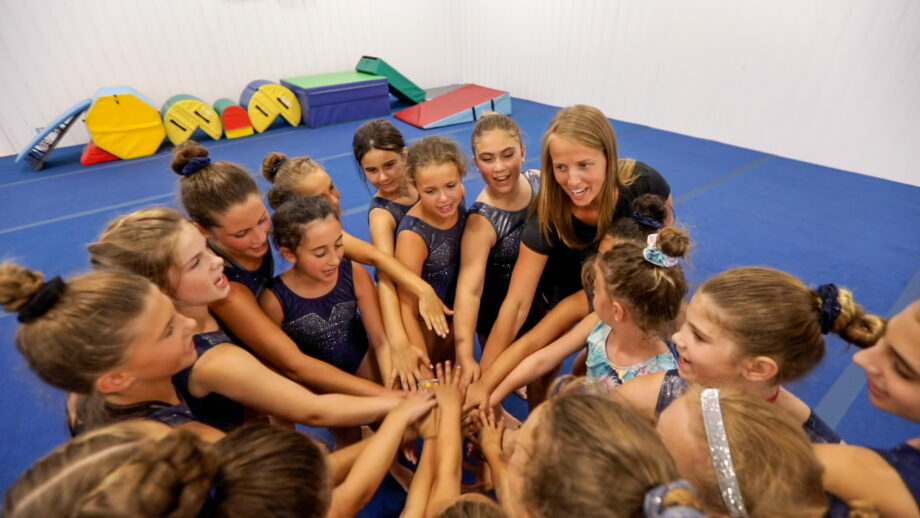 a group of girls with their hands in a team cheer.