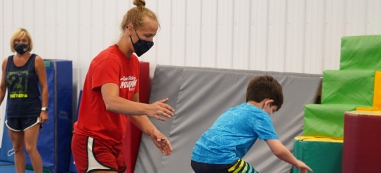 Coach Nastia in a mask helps a child do a backflip.